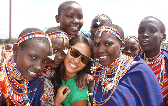 Student standing with Masai Mara people in Kenya