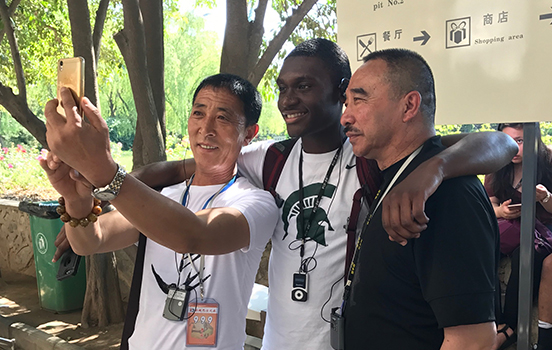 MSU student taking photo with local people in China