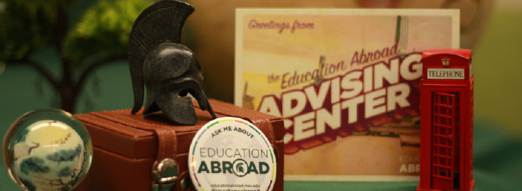 Photo of international souvenirs on a desk with Advising Center Contact info