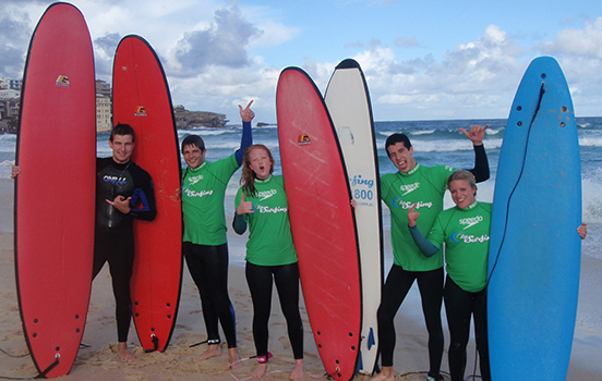 Students with surfboards on beach in Australia